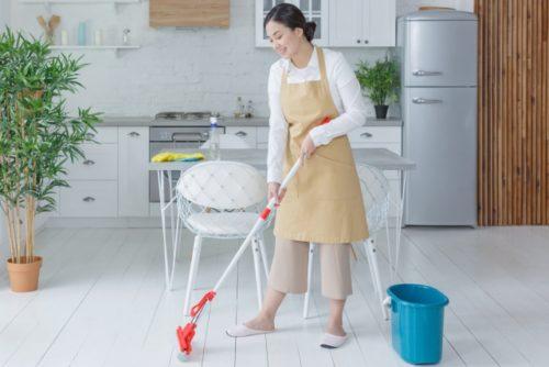 モップで床を掃除する女性
